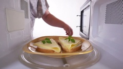 Placing toasts with cheese in the microwave oven Stock Footage