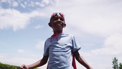 A young boy dressed as a superhero raises both arms in victory. Arkistovideo