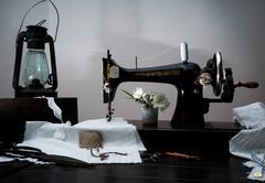 Classic retro style manual sewing machine ready for  work, kerosene lamp Stock Photos