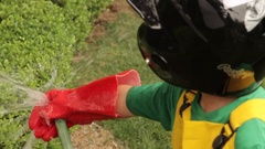 A boy wearing a red rubber glove blocks a garden hose's stream. Stock Footage