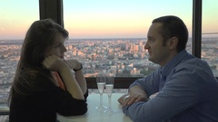 Man and woman celebrate on terrace restaurant, beautiful evening city view  Stock Footage