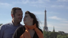 Portrait of happy couple laughing, eiffel tower in background, man whispering  Arkistovideo