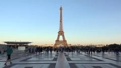 Eiffel tower on beautiful evening light, people passing on Trocadero Stock Footage