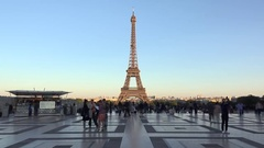 People passing fast close Eiffel tower, blue warm light Stock Footage