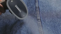Woman steaming denim fabric on ironing table Stock Footage