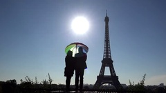 Romantic couple protected  by colored umbrella close Eiffel tower, sun shinning Stock Footage