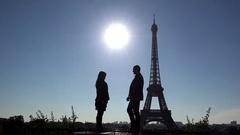 Romantic proposal close Eiffel tower, man on knees, sun shinning on blue sky Stock Footage