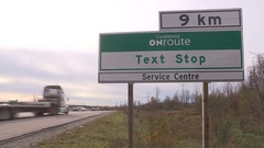 Anti texting and driving rest stop sign on highway Stock Footage