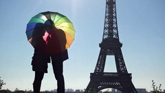 Lovers behind colored umbrella in front of Eiffel tower in Paris Stock Footage