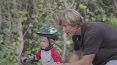 Father and son spend quality time, learning to ride a bike. Stock Footage
