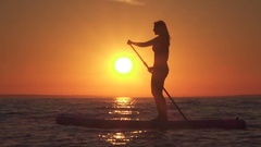 SLOW MOTION: Beautiful young female rider stand up paddle surfing at sunset Stock Footage