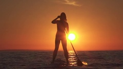 SLOW MOTION: Attractive young female rider stand up paddling into setting sun Stock Footage