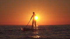 SLOW MOTION: Healthy young female rider stand up paddling at golden sunset Stock Footage