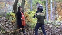 Father giving a piggy ride to his son kissing pregnant mother belly in autumn  Stock Footage