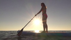 SLOW MOTION: Young girl enjoying ride on inflatable paddleboard at sunny morning Stock Footage
