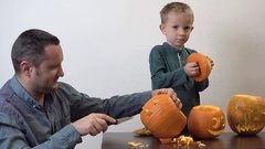 Father carving Halloween pumpkins, funny child singing and dancing Stock Footage