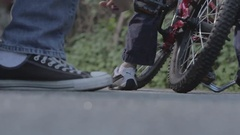 A father attaches and detaches training wheels in the front driveway. Stock Footage