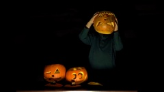 Little child with Halloween pumpkin as his head, dark background, funny boy Stock Footage