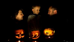 Young family with illuminated pumpkins heads, mother, father and child have fun  Stock Footage