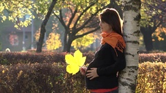 Attractive pregnant woman playing with yellow autumn leaf, touching belly, enjoy Stock Footage