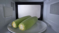 Cooking fresh sweet corn on the cob with the husk in the microwave Stock Footage