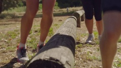 Group of people fitness training. Side jumps over a wooden log in the park Stock Footage