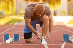 Male athlete tying laces for jogging. Stock Photos
