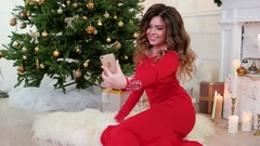 Christmas, pretty girl in holiday dress on the video calls says, wishes a Happy Stock Footage