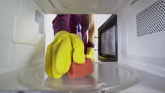 Cleaning microwave girl with sponge and cleaner wiping inside of the oven Stock Footage