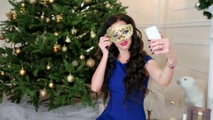 Christmas masquerade Beautiful girl in golden mask makes selfie mobile phone Stock Footage
