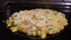 Slow Motion Cook flips Okonomiyaki Japanese food. Cooking Monjayaki Fried-Dan Stock Footage