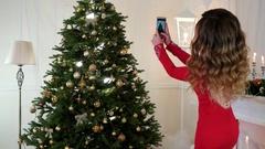 Christmas girl photographed on a mobile phone Christmas tree with toys Stock Footage