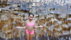 Cute little girl in swimsuit having fun under falling water before a stone wall Stock Footage
