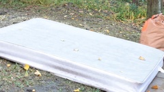 Mattress on the lawn for garbage Stock Footage