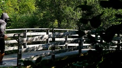 Hooded man running on wooden bridge in the wood, slow motion Stock Footage