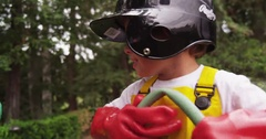 A young boy pranks his brother by folding a garden hose to block flow. version 2 Stock Footage