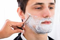 Close-up Of A Hairdresser Shaving Man's Beard By Applying Shaving Cream Stock Photos