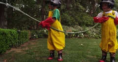 A little boy blocks a garden hose to prank his brother. Stock Footage