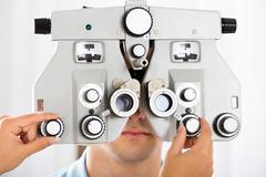 Close-up Of An Optometrist's Hand Adjusting Phoropter For Young Male Patient Stock Photos