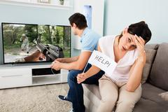 Upset Woman Holding Help Flag While Her Husband Busy Playing Game On Televisi Stock Photos