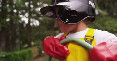 A young boy pranks his brother by folding a garden hose to block flow. Stock Footage