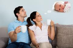 Happy Couple Dreaming Of Having Child Together While Sitting On Sofa At Home Stock Photos