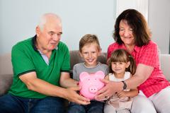 Family Saving Money Using Piggy Bank To Secure Kids Financial Future Stock Photos