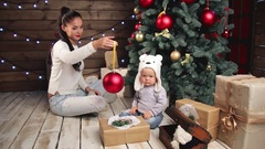 Mother and adorable baby decorating a ree Stock Footage