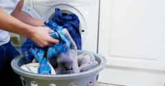 Man putting dirty clothes into washing machine Stock Footage