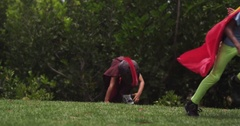 Two young superheroes crest over a hill while running. Slow motion. Stock Footage