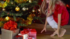 Kids open present at christmas time Stock Footage