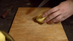Potato tuber is cut manually with a knife into slices on the Board. Stock Footage