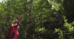 Child superheroes sprint uphill, into frame. Slow motion. Stock Footage