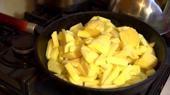 The glass lid puts the man's hand on a cast-iron frying pan with fried potatoes. Stock Footage